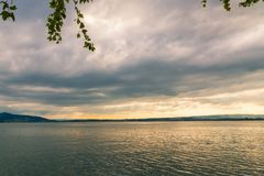 Sunset on lake with wooden pier on overcast day. Zug, Switzerland.  Royalty Free Stock Photo
