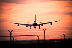 Sunset with landing airplane Royalty Free Stock Photography