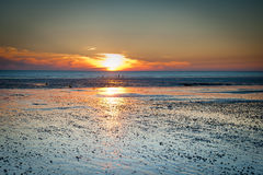 Sunset landscape on the beach during low tide Stock Images
