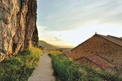 Sunset landscape with big rock and roofs in Ares. Stock Photography