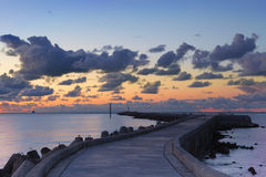 Sunset landscape with dark clouds and pier Royalty Free Stock Photos