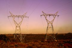 Sunset landscape with Electrical Pylons Stock Images