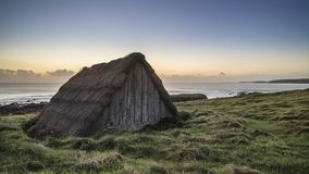 Sunset landscape image of seaweed drying hut at Freshwater West Royalty Free Stock Photos