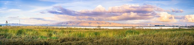 Panoramic sunset landscape of the marshes of south San Francisco bay, Mission Peak covered in sunset colored clouds. Sunset landscape of the marshes of south San Royalty Free Stock Photography