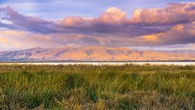 Sunset landscape of the marshes of south San Francisco bay, Mission Peak covered in sunset colored clouds, Sunnyvale, California. Sunset landscape of the marshes Stock Photo