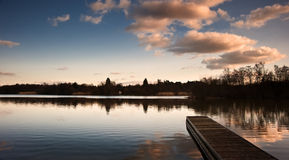 Sunset landscape over jetty on lake Royalty Free Stock Images
