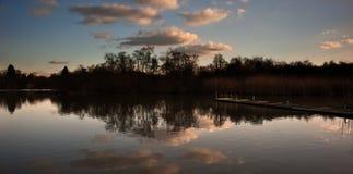 Sunset landscape over jetty on lake Stock Photo