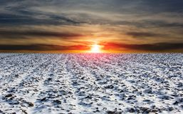 Sunset over winter meadow. Sunset landscape over winter plouged farm field Royalty Free Stock Photography