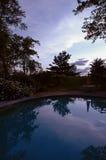 Sunset landscape reflected in pool. Peaceful backyard scene royalty free stock image
