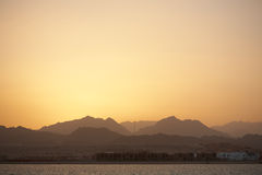Sunset landscape - sea, mountains, yellow sky Stock Photography