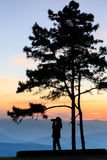 Sunset landscape with woman photographer silhouette. Stock Photos