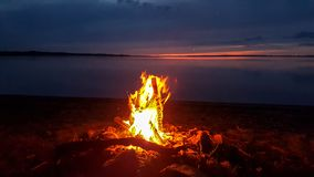 Sunset landscape with wood burning blaze in bonfire, tranquil lake and pink blue beautiful sky stock images