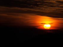 Sunset. Large sun behind the clouds fuzzy royalty free stock images
