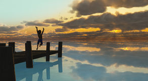 Sunset Leap A1. A joyful young boy jumps from a dock into a peaceful lake that reflects a striking, beautiful sunset Stock Photo