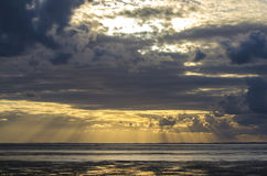 Sunset light through the clouds from the beach, Bay of Saint Mic Stock Images