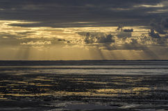 Sunset light through the clouds from the beach, Bay of Saint Mic Stock Photo