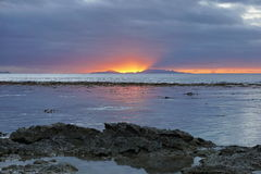 Sunset light with island at the horizon Pacific Royalty Free Stock Photography
