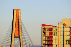 Sunset light over bridge tower and apartment building Stock Images