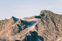 Sunset light over retiring dying glaciers on the Italian French Alps. Climate change concept. Toned desaturated image. Royalty Free Stock Images