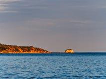 Sunset Light on Promontory and Rocky Islet, Greece. Sunset orange light highlighting a Gulf of Corinth Bay, Ormos Lemonias, promontory and rocky islet, Greece royalty free stock photo