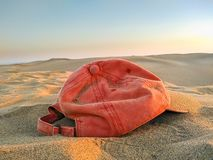 sunset light of a red cap abandoned or forgotten on the brown sand of dune of the desert by a tourist person on holidays. The wind royalty free stock image
