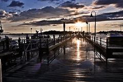 Sunset Light Reflecting on Wet Fishing Pier. This fishing pier with lobster boat resting for the night is reflecting the setting suns rays off the piers wet royalty free stock photo