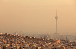 Sunset Light on Skyline of Air Polluted Tehran. Residential buildings in front of Milad Tower in air-polluted skyline of Tehran illuminated with golden sunset royalty free stock photo