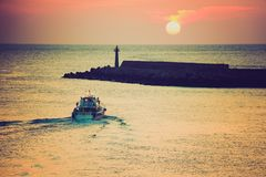 Sunset With Lighthouse and Boat Coming Toward Land Royalty Free Stock Photos