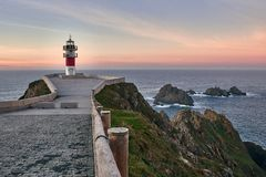 Sunset at a lighthouse on the edge of the cliff stock image