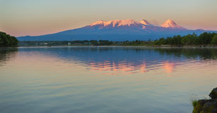 Sunset lighting Kluchevskaya group of volcanoes with reflection in river Kamchatka. Royalty Free Stock Images