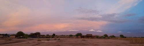Sunset lights in the arid and desolate landscape of the Atacama Desert. And the peaks of the snowy volcanoes of the Andes cordillera in the background royalty free stock photography