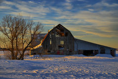 Sunset Lights Up Barn Interior. The setting sun's rays go through a hole in the roof of this old barn and light up the interior Stock Photo