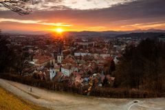 Sunset in Ljubljana on the last days of winter. A view, from the castle hill towards Trnovo. Of the setting sun over the hills on the west and under the clouds stock image