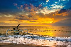 Sunset on the Lombok Indonesia. A fishing boat goes to the ocean in the evening. Bright colorful orange sun hidden in dense blue clouds over the Bali Sea. A Royalty Free Stock Photography