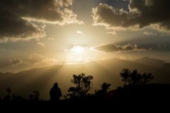 Sunset with a lonely silhouette. Sunset in the mountains with lonely person watching it Stock Photography