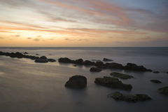 Sunset over Cap Gris Nez beach. Scenic view of sunset over Cap Gris Nez beach with silhouetted rocks in foreground, France Stock Photo
