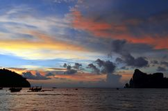 Sunset with long tail boats on Loh Dalum bay at Phi Phi island. Sunset on Loh Dalum bay at Koh Phi Phi, Andaman Sea, Krabi province, Thailand stock photo