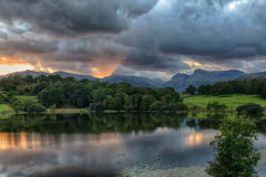 Sunset at Loughrigg Tarn in Lake District. Sun setting over Langdale Pikes with Loughrigg Tarn in foreground Stock Images