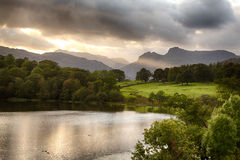 Sunset at Loughrigg Tarn in Lake District. Sun setting over Langdale Pikes with Loughrigg Tarn in foreground Royalty Free Stock Image