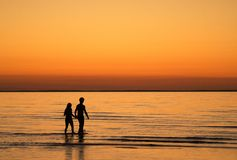 Sunset love. Two people holding hand in the sunset going for a night swim. Beach: Köpingbadens in Öland, sweden Royalty Free Stock Image