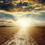 Sunset in low clouds over asphalt road with white line Stock Photography