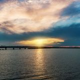 Sunset in low clouds over river with bridge. Sunset in low dark clouds over river with bridge Stock Photo