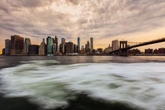 Sunset at Lower Manhattan Skyline, New York United States. Cloudy day sunset at Lower Manhattan Skyline view from Brooklyn Bridge Park, New York United States Stock Photo