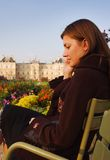 Sunset in Luxembourg garden. Pretty young woman speaking on her mobile phone while sitting in Luxembourg garden (Paris) in sunset. Blurred Luxembourg palace in stock photos
