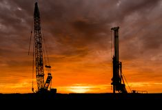 Sunset Machines. Crane and a drill standing tall at sunset royalty free stock image