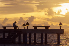 Sunset in Madoogali. Pier at sunset in Madoogali Island (Maldives) with a man in meditation Royalty Free Stock Photography