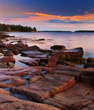 Sunset on Maine Coast with Glowing Granite. Sunset on the rocky Maine coast with a beautiful blue and orange sky. The pink granite rocks are lit by the setting royalty free stock photography