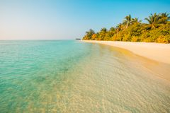 Tropical sunset landscape. Beach sunset in Maldives island with luxury water villas and long wooden pier Stock Images