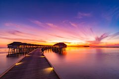Sunset on Maldives island, luxury water villas resort and wooden pier. Beautiful sky and clouds and beach background for summer va