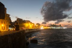 Sunset at Malecon, the famous Havana promenades. Cuba. At the bo. HAVANA, CUBA- JANUARY 15 2017: Sunset at Malecon, the famous Havana promenades where Habaneros Stock Photos